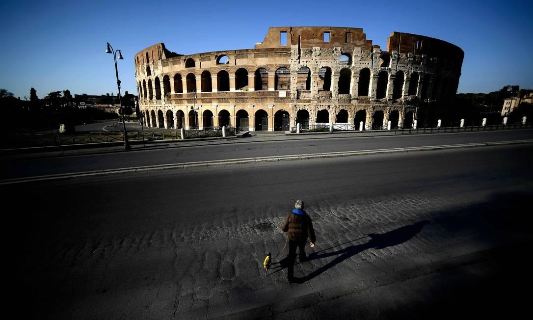 Homem caminha com cachorro em frente ao Coliseu, em Roma, na Itália Foto: FILIPPO MONTEFORTE / AFP