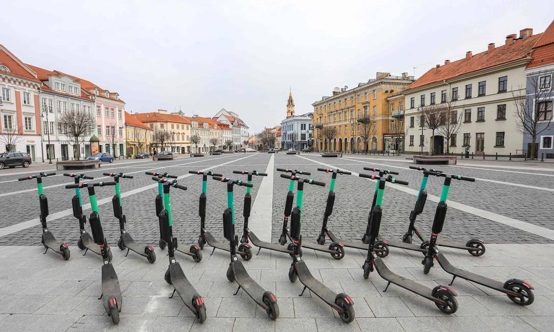 Patinetes elétricos abandonados numa praça na parte antiga de Vilnius, capital da Lituânia Foto: PETRAS MALUKAS / AFP