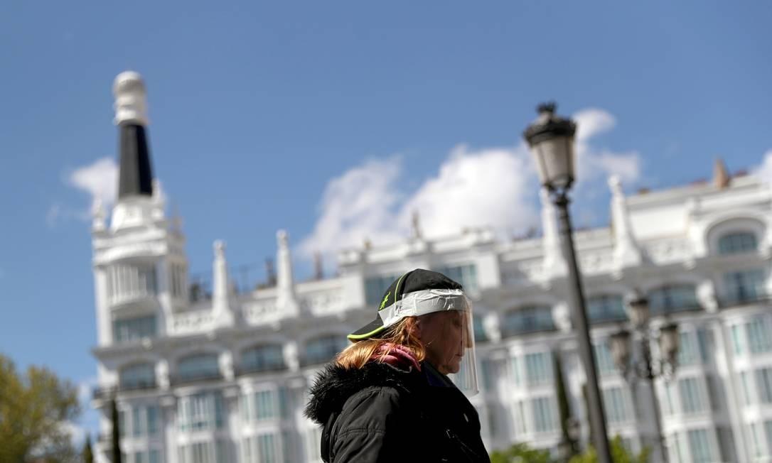 Mulher usando máscara de proteção caseira caminha nas ruas de Madri, na Espanha Foto: SUSANA VERA / REUTERS/04-04-2020