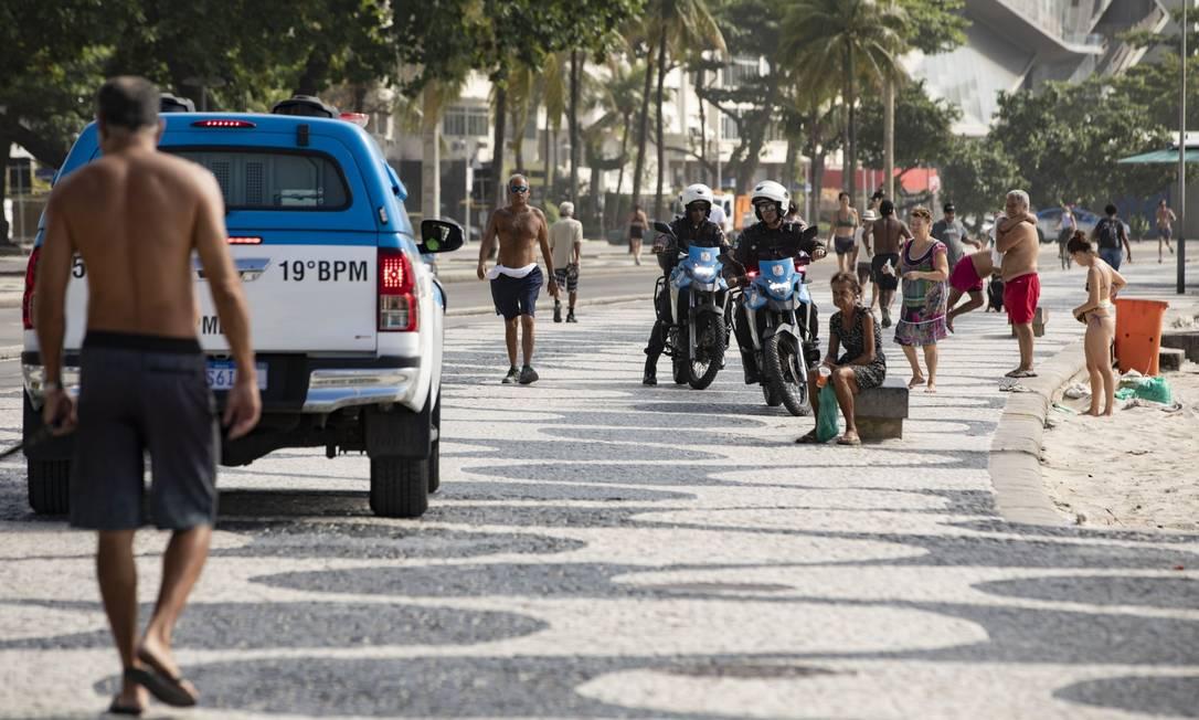 Policiais e Guarda Municipal atuam na Orla de Copacabana tentando conter pessoas na calçada e retirando banhistas da areia no fim de semana Foto: Ana Branco / Agência O Globo
