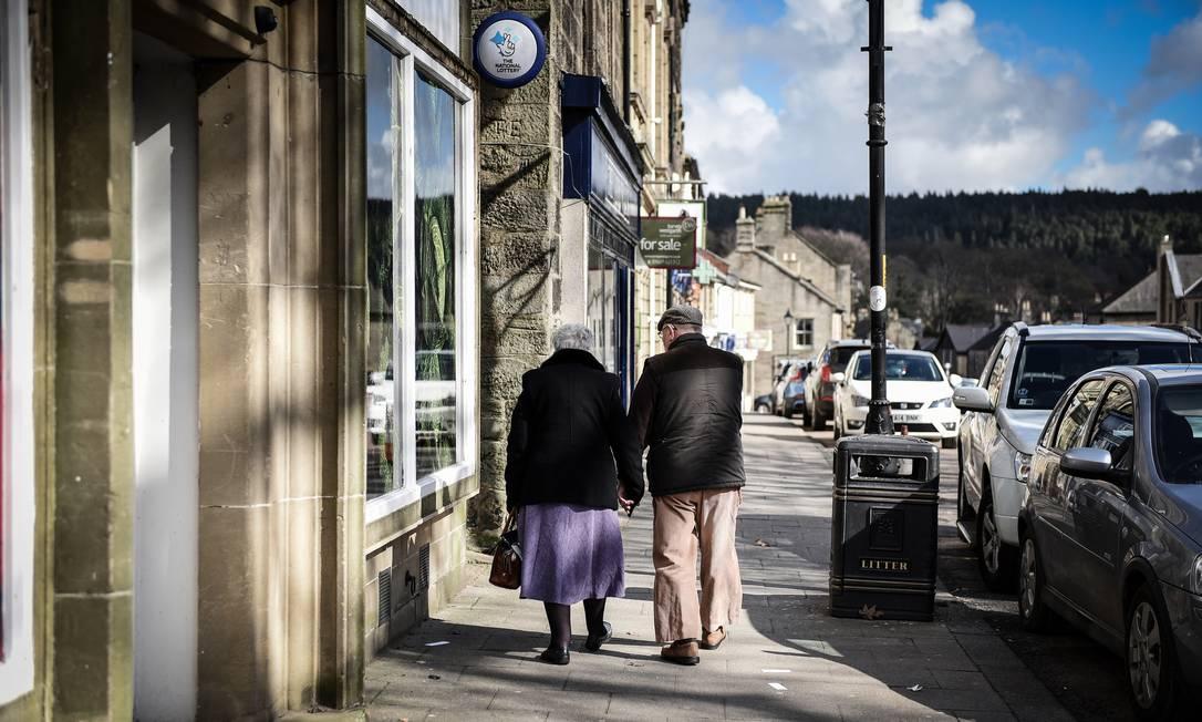 Casal de idosos caminha pelas ruas de Rothbury, no Reino Unido Foto: MARY TURNER / NYT/20-03-2020