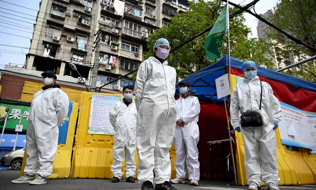 Voluntários na cidade de Wuhan observam três minutos de silêncio em homenagem às pessoas que morreram no combate ao coronavírus na China Foto: NOEL CELIS / AFP