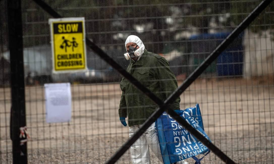 Homem usa uma máscara de proteção enquanto anda no camp0 de Malakasa, espaço destinado a refugiados. Foto: ANGELOS TZORTZINIS / AFP