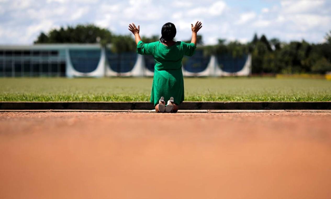 De joelhos, mulher evangélica e admiradora do presidente Jair Bolsonaro faz uma oração em frente ao Palácio da Alvorada enquanto casos do novo coronavírus continuam a subir no Brasil Foto: ADRIANO MACHADO / REUTERS