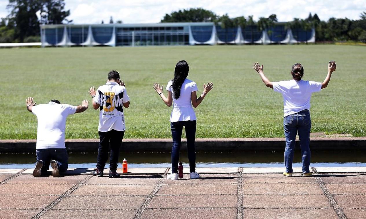 Populares rezam em frente ao Palácio da Alvorada, em Brasília, neste domingo (5), em meio à pandemia de Covid-19 Foto: Jorge William / Agência O Globo