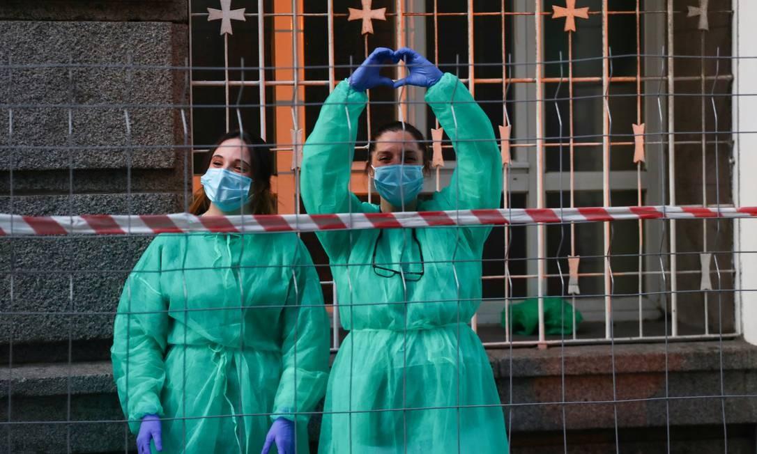 Médicas do hospital La Princesa agradecem a aplausos de moradores em Madri: desaceleração dos casos de coronavírus Foto: SERGIO PEREZ / REUTERS