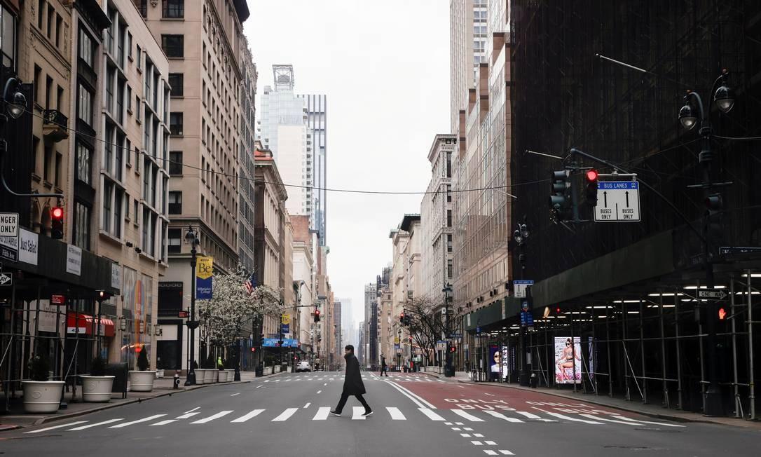 Homem atravessa a 5ª Avenida quase vazia no centro de Manhattan durante o surto de coronavírus na cidade de Nova York, EUA Foto: MIKE SEGAR / Reuters