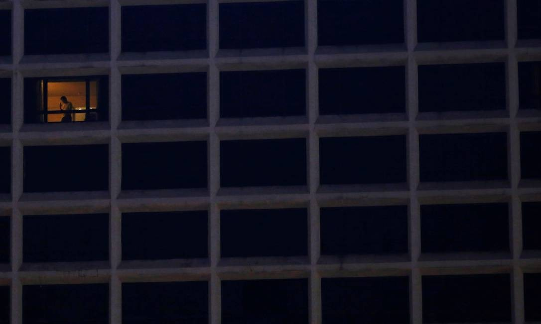 Um hóspede fala em seu celular, em um hotel, durante o surto da doença em Hong Kong Foto: TYRONE SIU / REUTERS