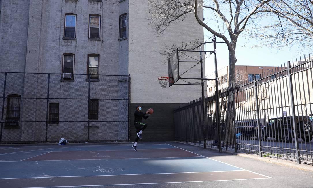Um jovem joga basquete sozinho e usa uma máscara protetora em Manhattan, Nova York Foto: CAITLIN OCHS / REUTERS
