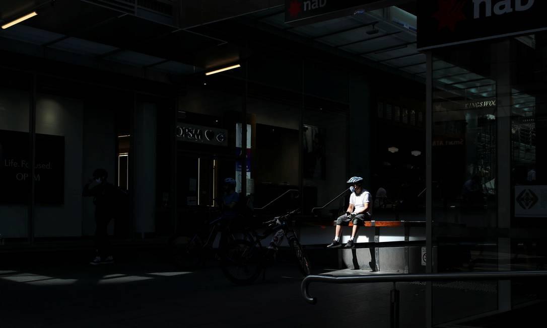 Um entregador, de bicicleta, usa uma máscara facial durante a implementação de regras mais rígidas de distanciamento social e autoisolamento para limitar a propagação da doença por coronavírus em Sydney, Austrália Foto: LOREN ELLIOTT / REUTERS