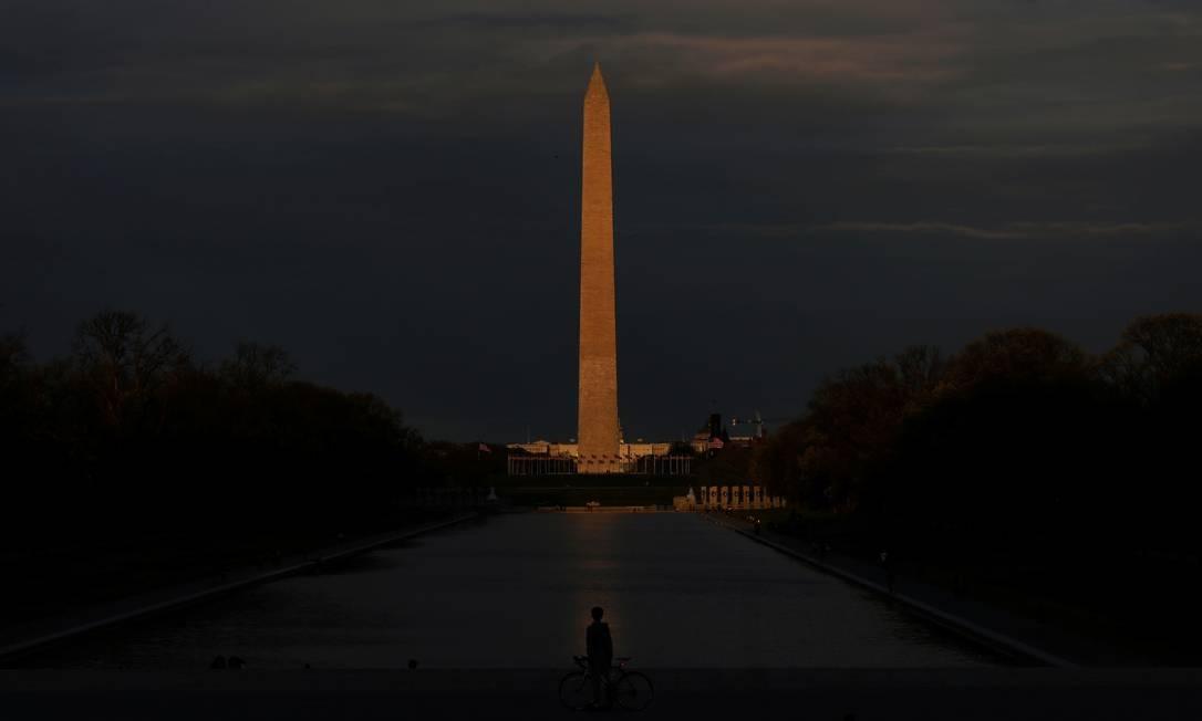 Um ciclista para em frente ao Lincoln Memorial e Espelho D'Água, com o Monumento de Washington iluminado pelo pôr do sol na parte traseira, enquanto a propagação da Covid-19 continua em Washington, EUA Foto: LEAH MILLIS / REUTERS