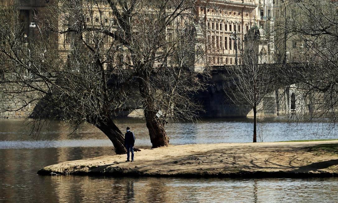 Um homem usando uma máscara facial fica em um parque vazio, Praga, República Tcheca Foto: DAVID W CERNY / REUTERS