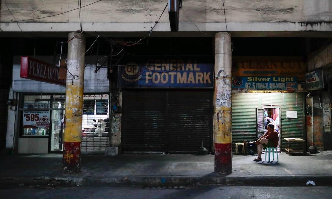 Um homem fica do lado de fora de lojas fechadas após o bloqueio na capital das Filipinas para impedir a propagação da Covid-19, em Manila, capital do país Foto: ELOISA LOPEZ / REUTERS