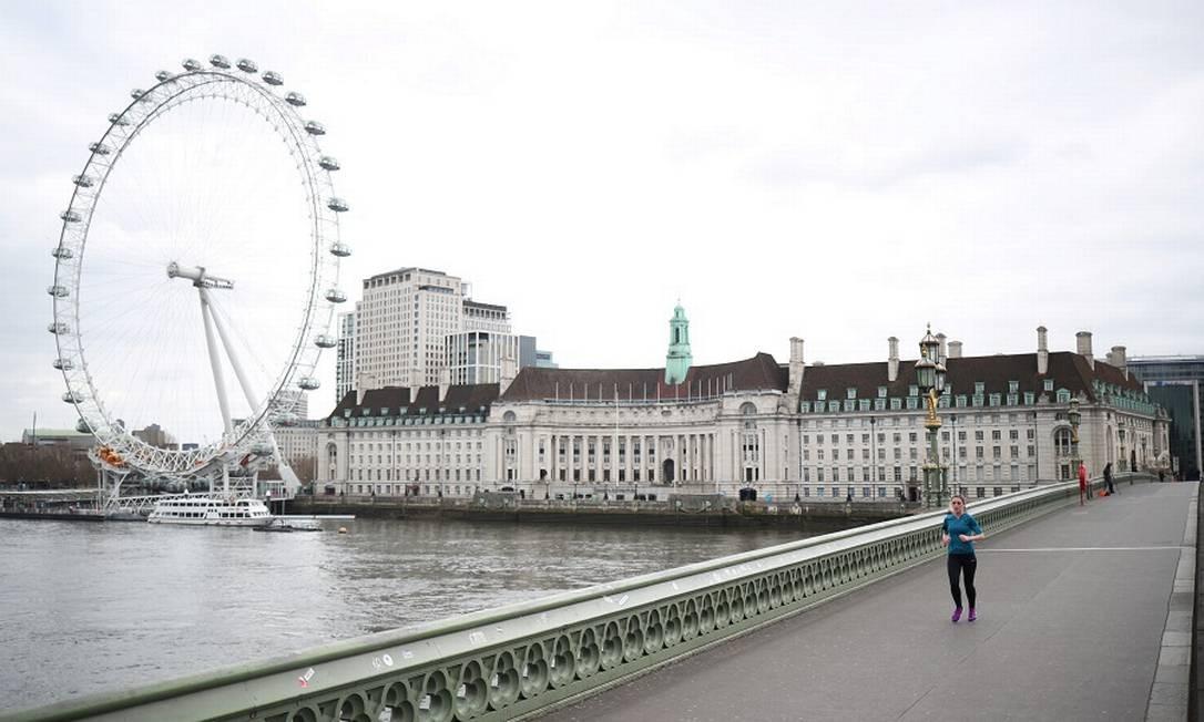 Mulher atravessa a Ponte de Westminster, vazia. Reino Unido liberou 418 bilhões de libras para minorar efeitos da pandemia. Foto: HANNAH MCKAY / REUTERS