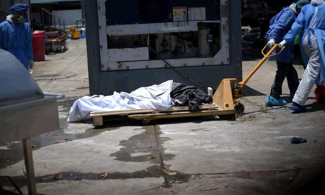 Funcionários retiram um cadáver da calçada do Hospital Teodoro Maldonado Carbo, em Guayaquil, no Equador Foto: Reuters