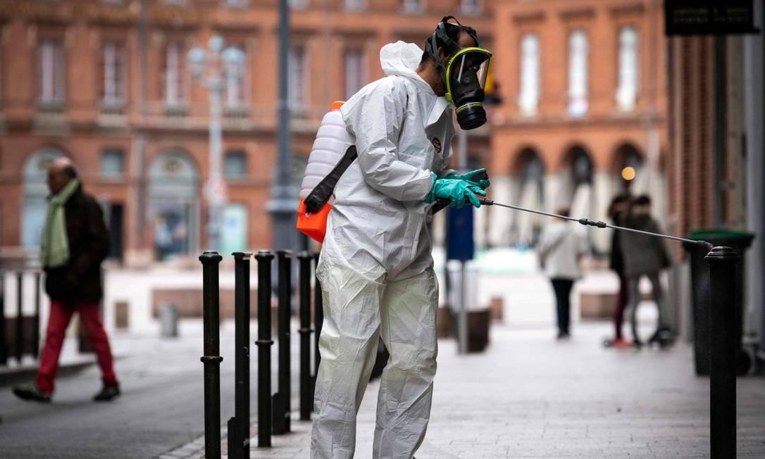 Homem com roupa de proteção desinfecta rua em Tolouse, na França Foto: LIONEL BONAVENTURE / AFP