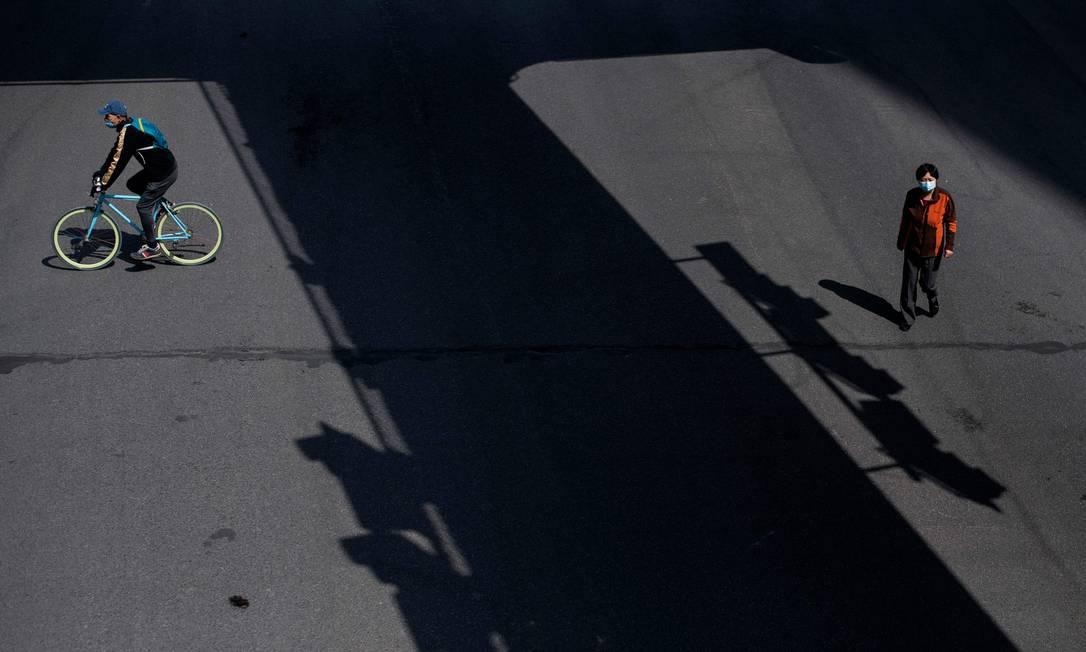 Ciclista e pedestre usam máscara protetora em rua de Wuhan, na China Foto: NOEL CELIS / AFP