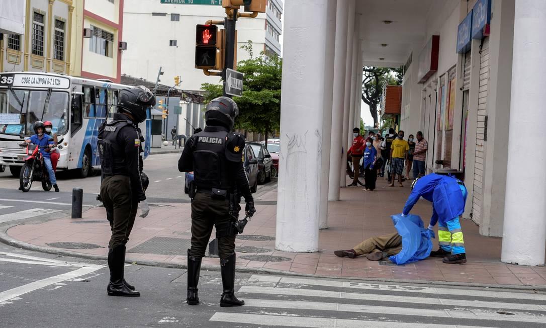 Tragédia. Paramédico cobre corpo de homem morto no centro de Guayaquil, segunda maior cidade do Equador Foto: Vicente Gaibor del Pino / REUTERS