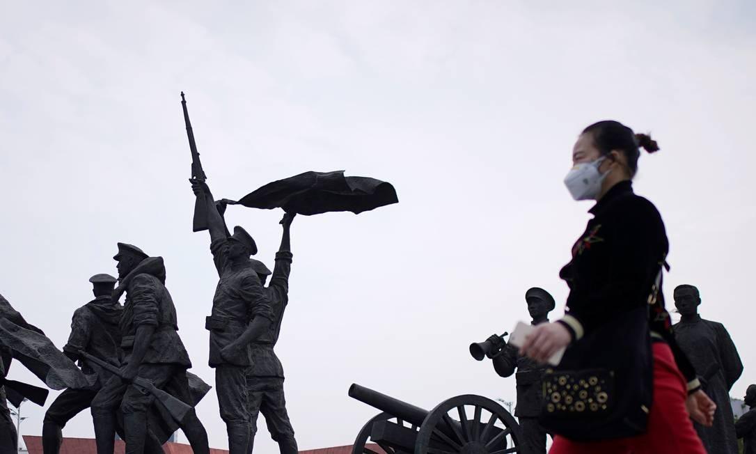 Pessoa de máscara passa por monumento da Revolução Xinhai em Wuhan Foto: ALY SONG / REUTERS