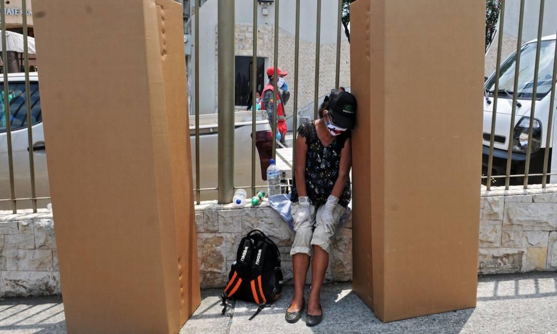 Mulher de máscara e luvas vela a caixa usada como caixão em Guayaquil, Equador Foto: JOSE SANCHEZ / AFP