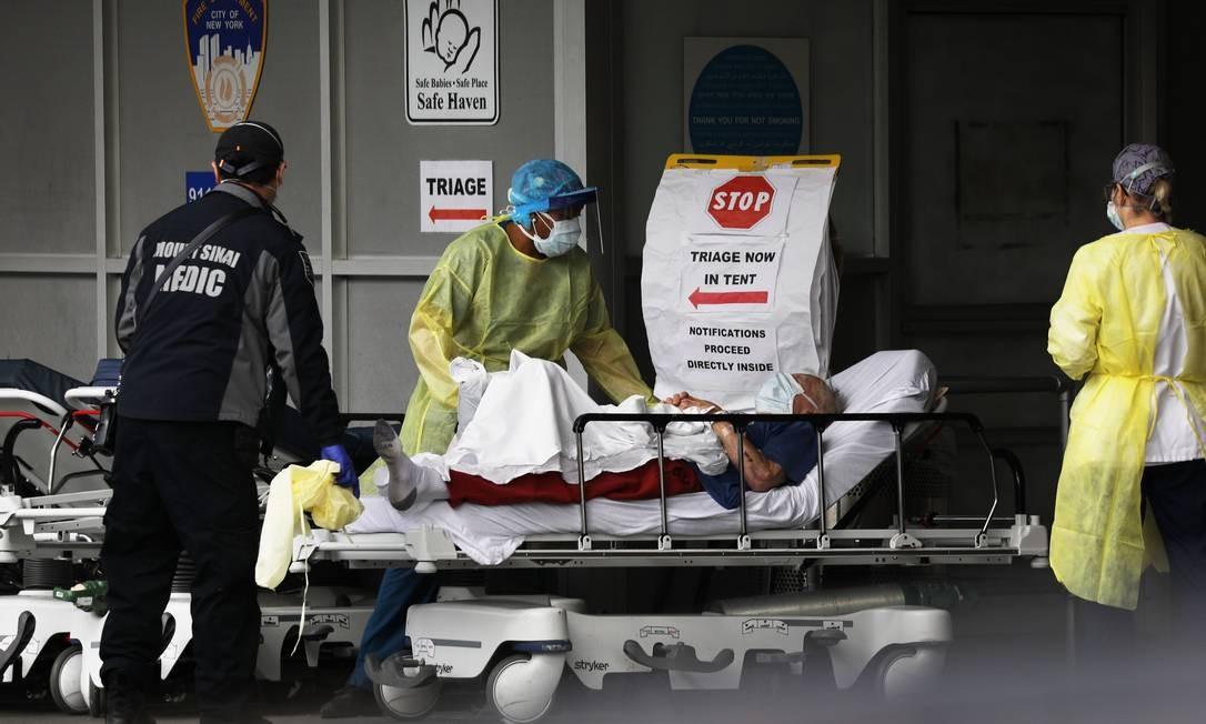 Profissionais de saúde atendem paciente em hospital de campanha no Brooklyn, em Nova York, epicentro da Covid-19 nos Estados Unidos Foto: SPENCER PLATT / AFP