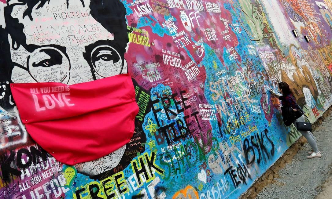 """Intervenção urbana 'veste' máscara de proteção no rosto de John Lennon, no incônico mural dedicado ao integrante dos Beatles, em Praga, na República Tcheca. O pano vermelho leva também gravado """"All You Need Is Love"""", um dos grandes sucessos da banda britânica Foto: DAVID W CERNY / REUTERS"""
