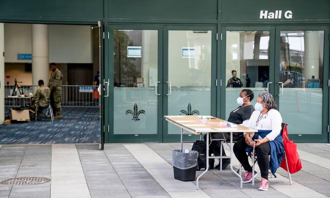 Funcionárias do departamento de Saúde da Louisiana medem a temperatura das pessoas na entrada de um centro de convenções que serve de hospital de campanha em Nova Orléans Foto: CLAIRE BANGSER / AFP