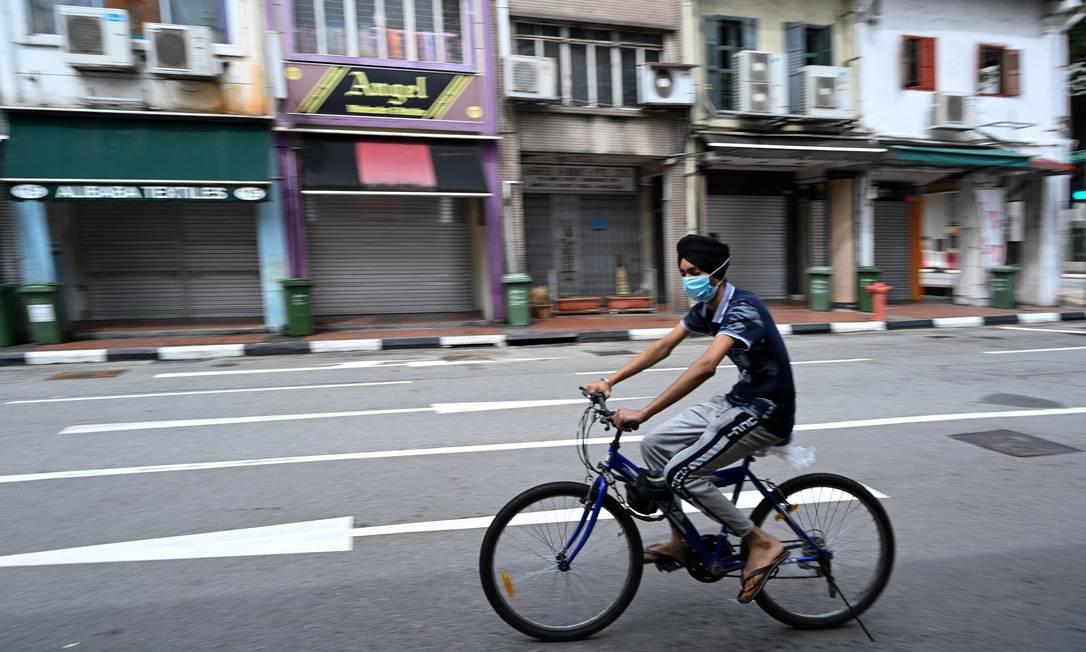 Homem usando máscara em uma das já vazias ruas de Cingapura. Maior parte das atividades da cidade está suspensa e as autoridades aplicam multas em quem violar as regras Foto: ROSLAN RAHMAN / AFP