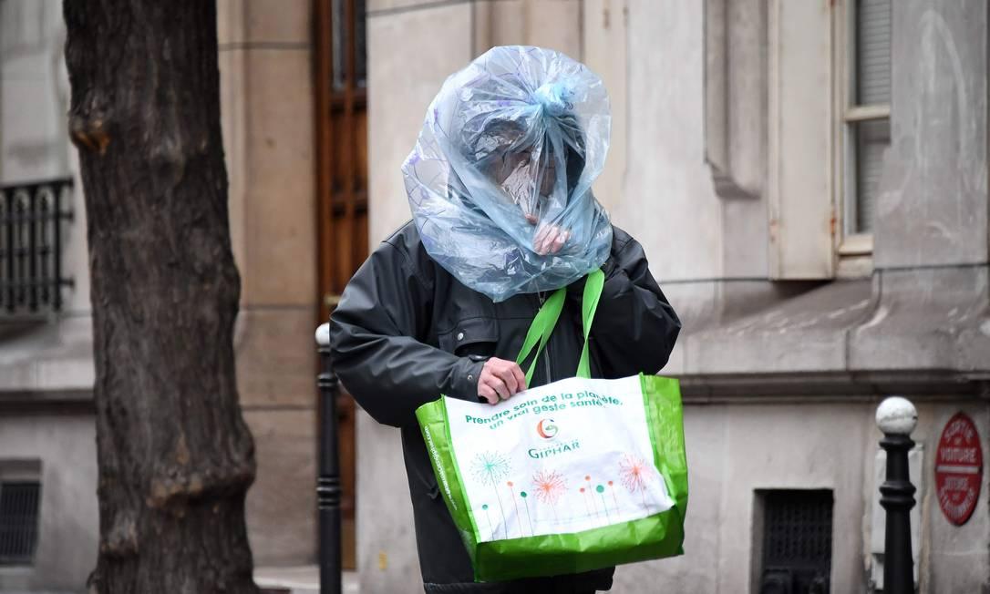 Homem protege seu rosto com uma sacola plástica enquanto caminha pelas ruas de Paris Foto: FRANCK FIFE / AFP