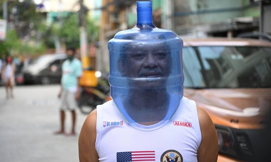 Homem usa máscara improvisada feito de um galão d'água para se proteger da Covid-19, em Manila, Filipinas Foto: TED ALJIBE / AFP