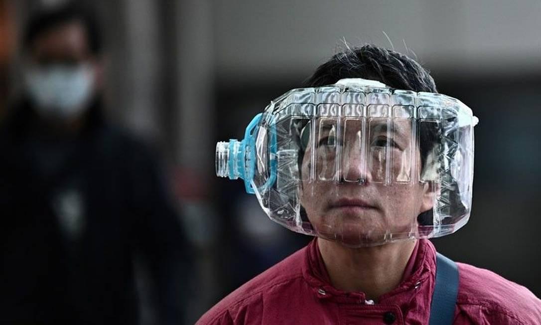 Homem cobre rosto com uma garrafa de plástico improvisada como máscara facial, em Hong Kong Foto: Anthony WALLACE / AFP