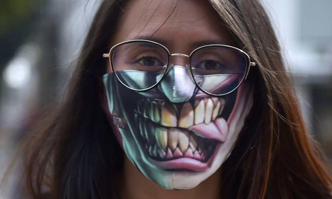 Mulher usa máscara facial como medida preventiva contra a propagação da Covid-19, em Bogotá, Colômbia Foto: RAUL ARBOLEDA / AFP