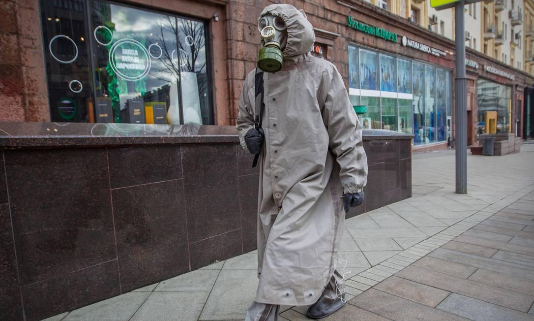 Homem veste um traje de proteção e uma máscara de gás enquanto caminha por uma rua no centro de Moscou, na Rússia Foto: STRINGER / AFP