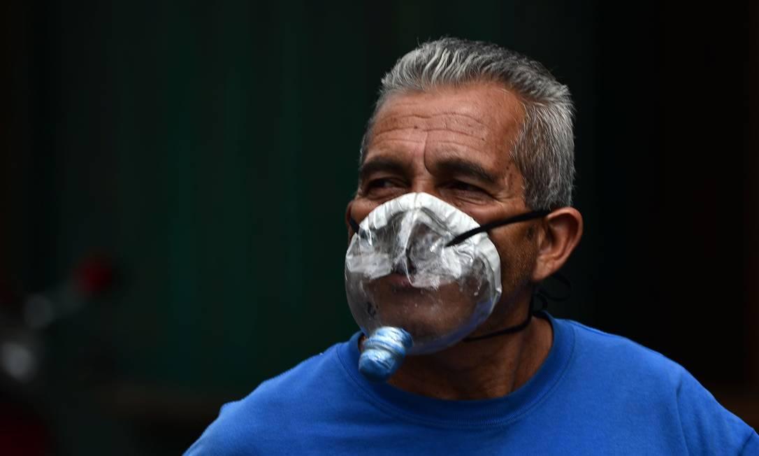 Homem hondureinho usa máscara improvisada feita de garrafa de plástico, na Tegucigalpa, Honduras Foto: ORLANDO SIERRA / AFP