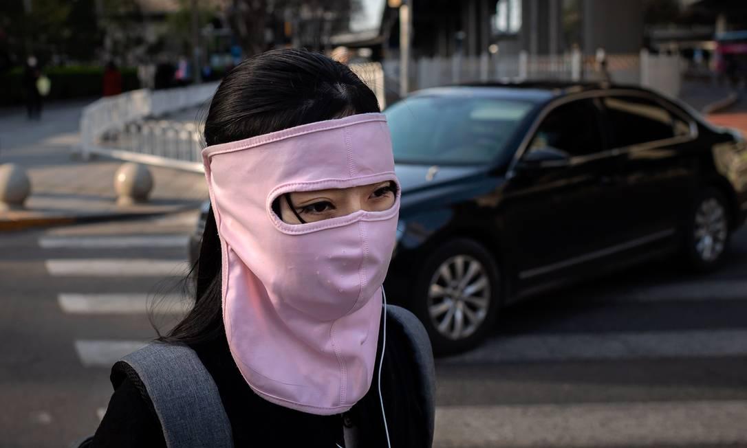 Mulher usa máscara cobrindo todo rosto em Pequin, China Foto: NICOLAS ASFOURI / AFP