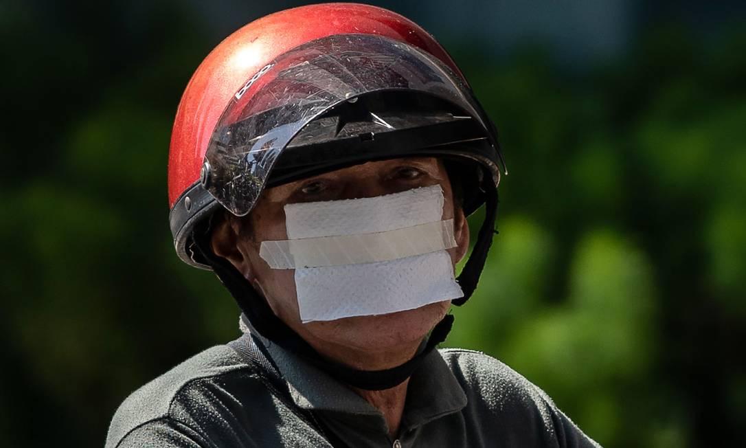 Homem improvisa máscara com pedaço de pano e esparadrapo, na Malasia Foto: MOHD RASFAN / AFP