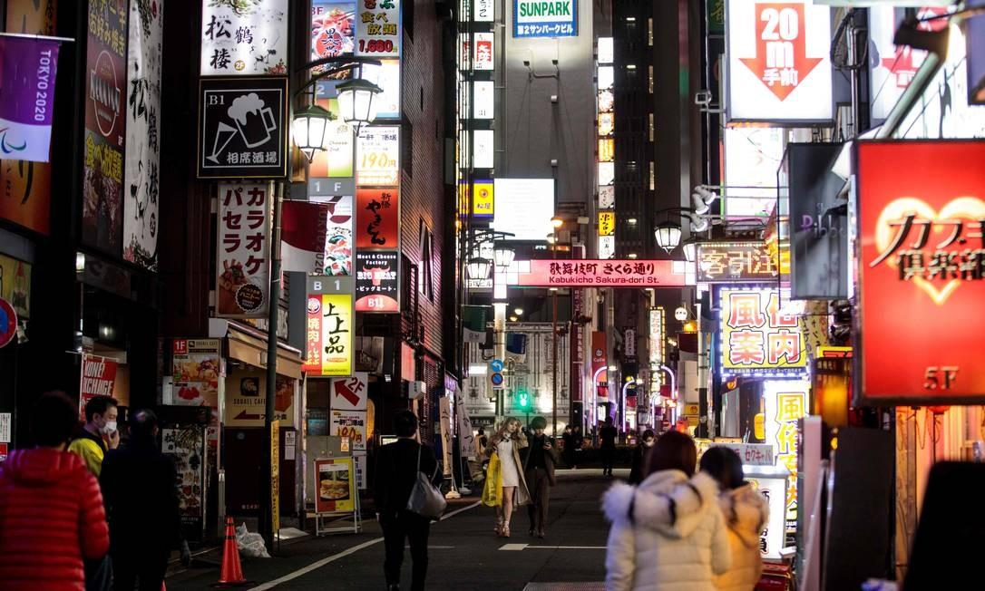 Pessoas caminham no distrito de Kabukicho, em Tóquio Foto: BEHROUZ MEHRI / AFP
