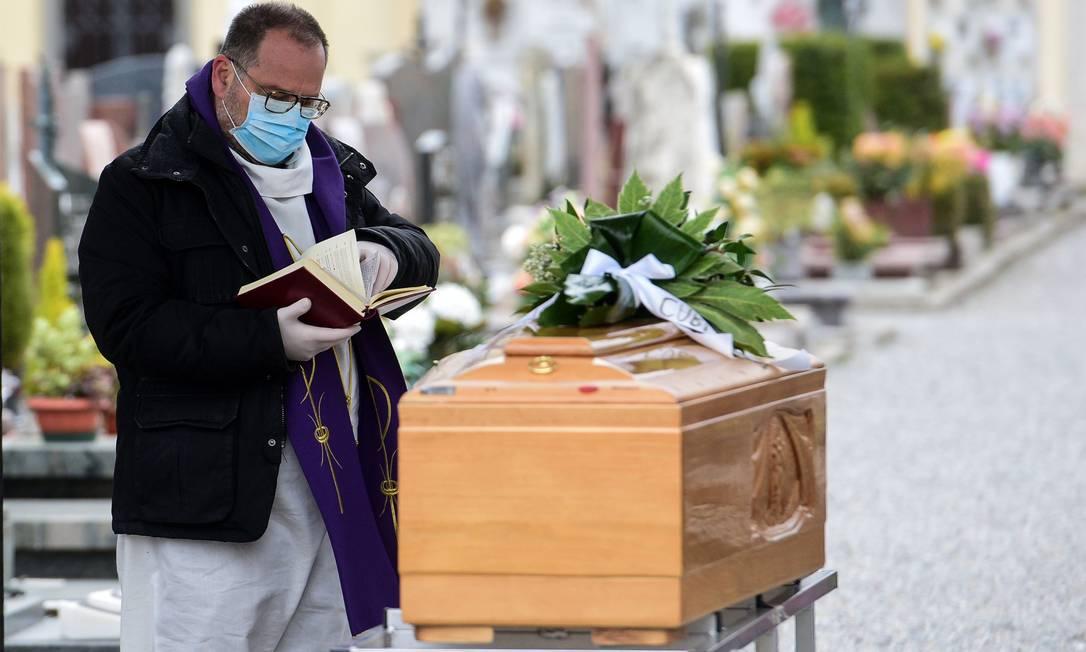 Padre de máscara faz bênçãos diante de caixão, na região da Lombardia, uma das mais afetadas pelo coronavírus na Itália Foto: PIERO CRUCIATTI / AFP