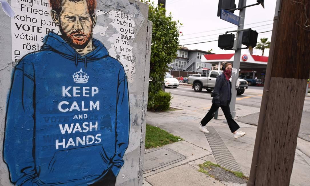 """Príncipe Harry é reproduzido em grafite em Los Angeles, Califórnia, nos EUA, vestindo um casaco com a frase """"fique calmo e lave as mãos"""", uma mensagem de conscientização em referência à campanha motivacional de autoria anônima """"fique calmo e siga em frente"""" (keep calm and carry on), que se espalhou pelo Reino Unido durante a Segunda Guerra Foto: ROBYN BECK / AFP"""