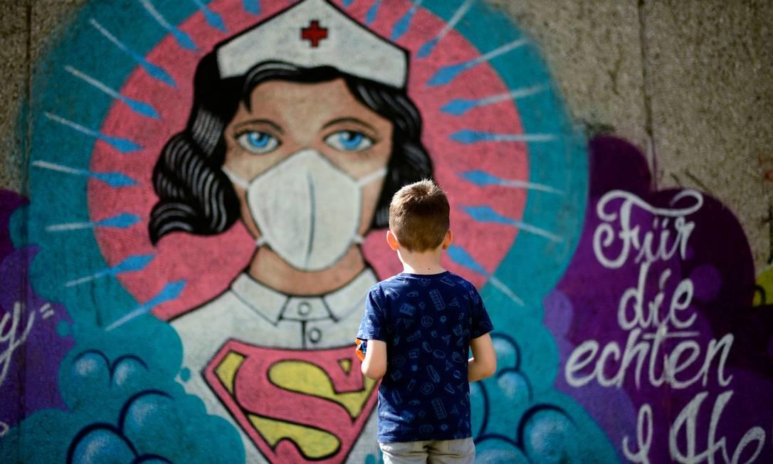 Garoto observa grafite pintado pelo artista Kai 'Uzey' Wohlgemuth, de uma enfermeira representada como Supermulher em muro na cidade de Hamm, oeste da Alemanha Foto: INA FASSBENDER / AFP