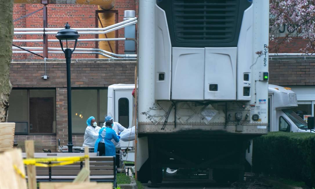 Funcionários de hospital em Nova York carregam corpo de vítima da Covid-19 para caminhão refrigerado Foto: David Dee Delgado / AFP