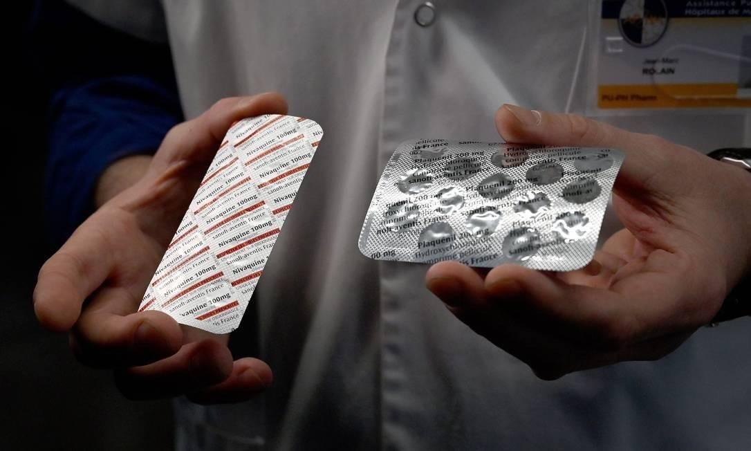Médicos exibem embalagens de cloroquina e de hidroxicloroquina Foto: GERARD JULIEN / AFP