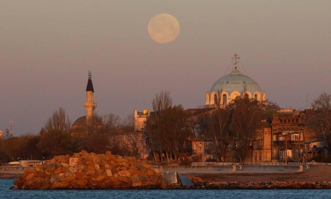 Superlua rosa atrás de uma mesquita e de uma catedral ortodoxa durante o nascer do sol em Yevpatoriya, na Crimeia Foto: ALEXEY PAVLISHAK / REUTERS