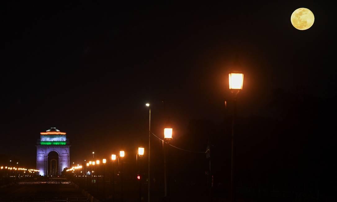 Lua cheia é retratada enquanto o portão da Índia é iluminado com as cores da bandeira nacional indiana, vistas de um Rajpath deserto durante um bloqueio nacional imposto pelo governo como uma medida preventiva contra a Covid-19 em Nova Délhi Foto: SAJJAD HUSSAIN / AFP