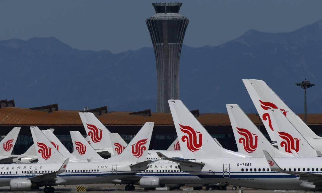 Aviões da Air China estacionados no pátio do aeroporto de Pequim Foto: Greg Baker / AFP