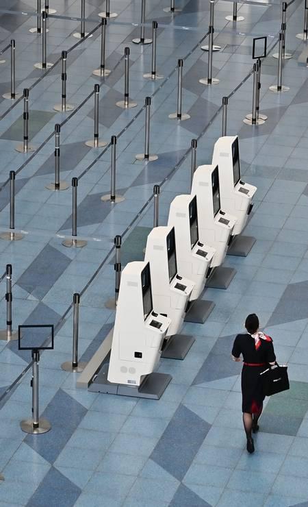 Uma comissária de bordo caminha, sozinha, por um salão deserto do aeroporto de Haneda, em Tóquio Foto: Charly Triballeau / AFP