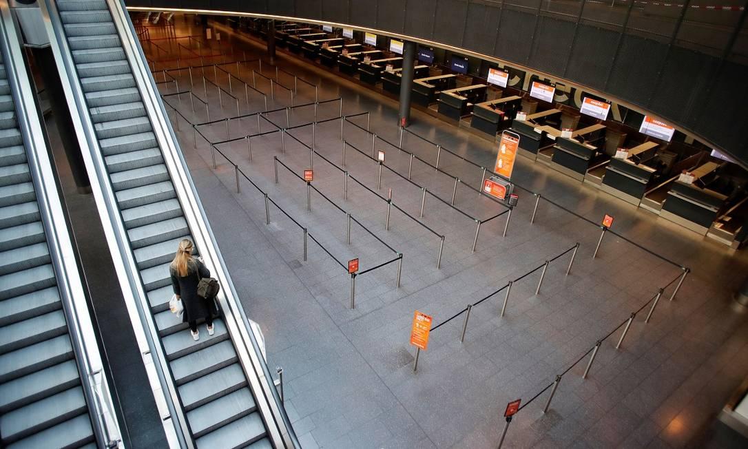 Passageira quase sozinha no aeroporto de Zurique, na Suíça Foto: Arnd Wiegmann / Reuters