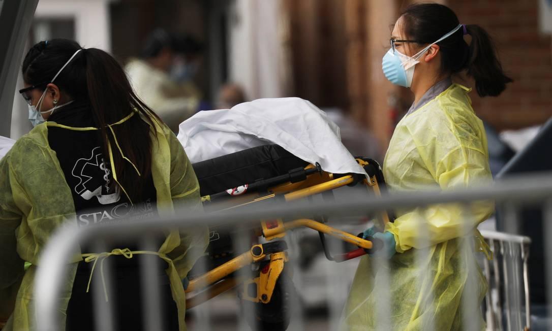 Profissionais de saúde fazem a transferência de pacientes entre hospitais de Nova York Foto: SPENCER PLATT / AFP