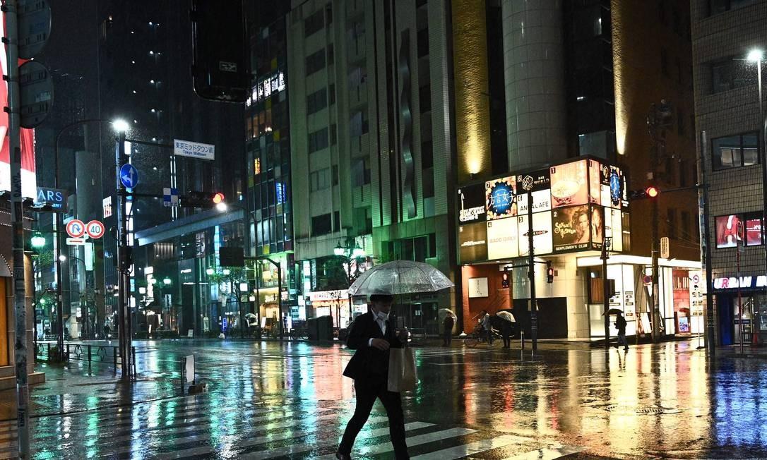 Homem usando máscara de proteção caminha com seu guarda-chuva no distrito de Roppongi, em Tóquio Foto: PHILIP FONG / AFP/09-04-2020