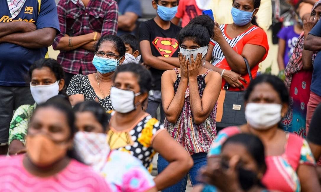 Moradores de condomínio com máscaras protetoras em Colombo, no Sri Lanka. Foto: ISHARA S. KODIKARA / AFP